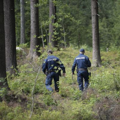Kaksi poliisia kävelee maastossa.