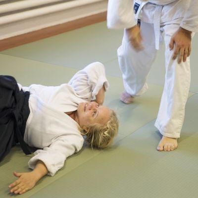 Kikka Niittyaho makaa tatamilla aikido-puvussa ja katsoo pariaan, joka hänet maahan on heittänyt.