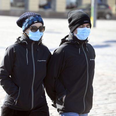 Ett par med munskydd promenerar i Helsingfors centrum.