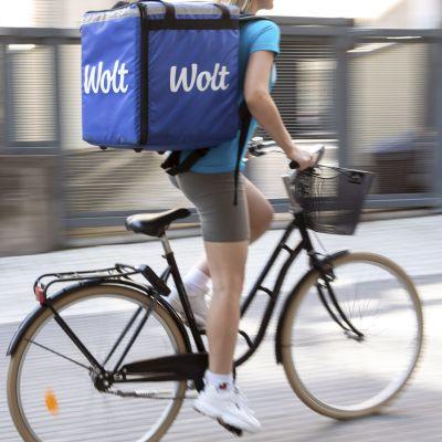 Cykelbud i shorts med stort matpaket på ryggen.