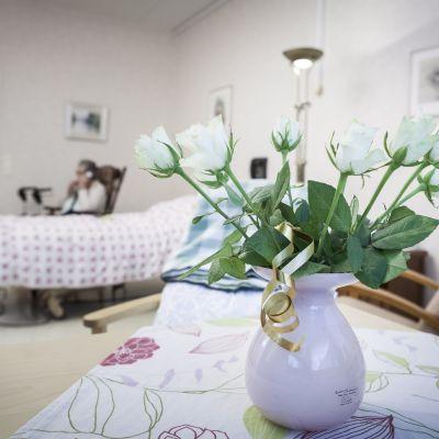 Blomkruka med vita rosor vid bäddavdelning i Helsingfors.
