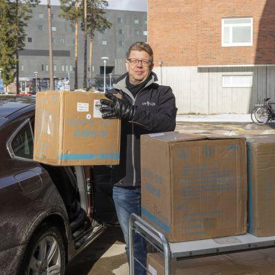 Kari Piltonen nostaa laatikoita autosta