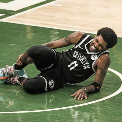 Kyrie Irving makaa loukkaantuneena maassa.