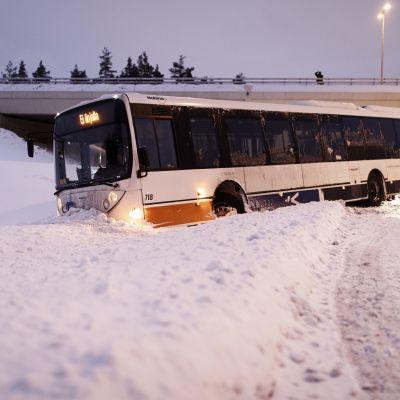 Buss som fastnat i snöhög.