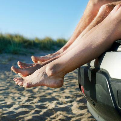 Två par bara ben som hänger ut ur en backlucka på en bil vid en sandstrand.