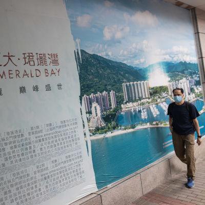 Mannen till höger passerar en reklamaffisch i bakgrunden av ett byggprojekt med höghus.