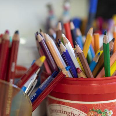 Taiteilijan värikkäitä puuvärikyniä purnukassa