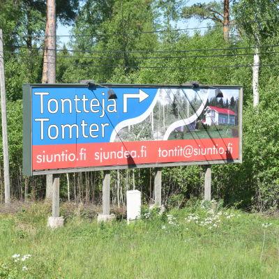 en skylt längs en väg där det står tomter till salu på svenska och finska och sedan sjundeå.fi, siuntio.fi