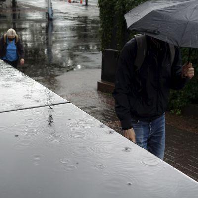 Jalankulkijoita sateisessa Ruoholahdessa Helsingissä 21. elokuuta.
