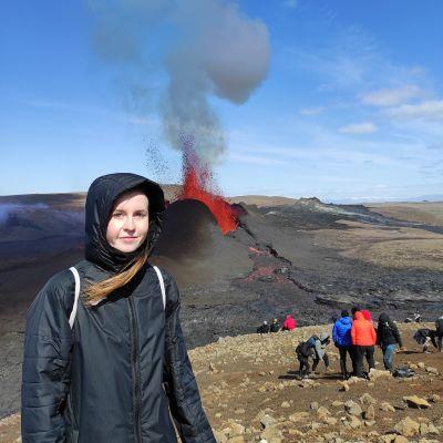 Kuvassa Vera Mattila seisoo taustallaan laavaa syöksevä tulivuori