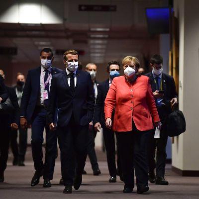 Angela Merkel och Emmanuel Macron går i en mörk korridor i Europabyggnaden. Båda har munskydd.