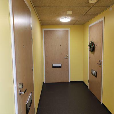 Kuva rappukäytävästä ja ovista, joista yhdessä on kranssi