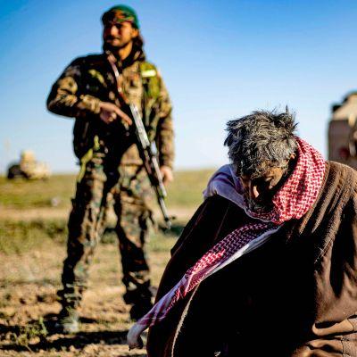 Tillfångagna misstänkta IS-medlemmar bevakas av en SDF-soldat