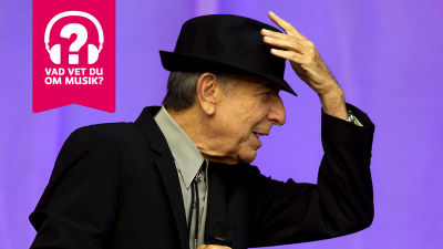 Leonard Cohen håller i sin hatt som är på huvudet.