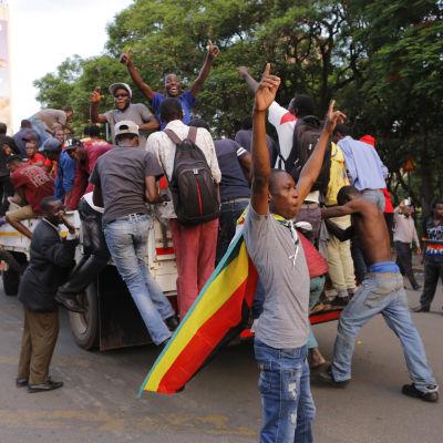 Folk på gatornai Herare firar Mugabes avgång.