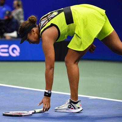 Naomi Osaka plockar upp sitt racket.