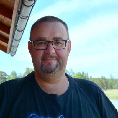 Dan Eriksson i svart t-skjorta utomhus med hav och natur i bakgrunden.