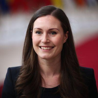 Sanna Marin ler stort när hon anländer till ett EU-möte i Bryssel den 12 december.