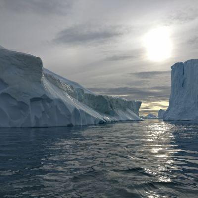 Isberg i mörkblått vatten med solnedgång i bakgrunden.