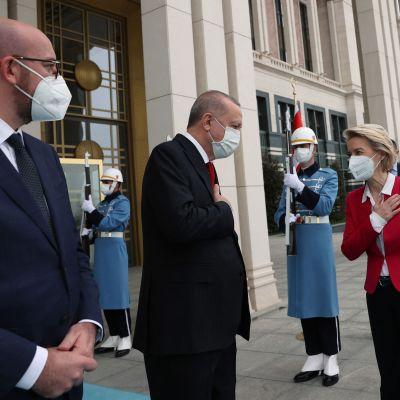 Två kostymklädda män och en kvinna i röd jacka och svarta byxor står utanför en byggnad med två soldater med gevär och långa ljusblå vapenrockar bakom sig. Alla bär munskydd. Från vänster Charles Michel, Recep Tayyip Erdogan och Ursula von der Leyen.