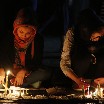 Två afghanska kvinnor tänder ljus under en minnesstund som ordnades för de som dödats i bombattacken i Kabul där minst 80 personer miste livet.