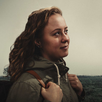 Kuvassa Hanna Asikainen seisoo utuisella niityllä reppu selässä.