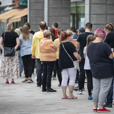 Nuoria ja heidän huoltajiaan jonottaa koronarokotukseen pitkässä jonossa Kouvolan kävelykadulla