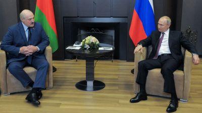 Aleksandr Lukasjenko och Vladimir Putin sitter bredvid varandra och tittar på varandra. I bakgrunden syns ländernas flaggor.