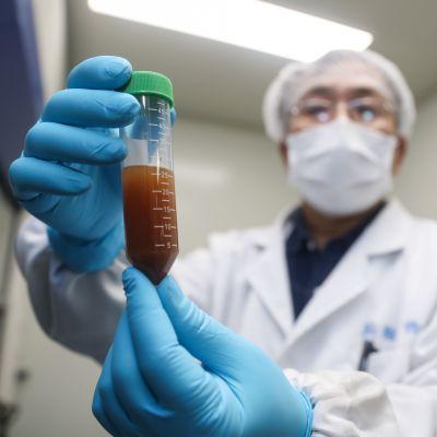 En person i skyddmask och vit läkarrock visar upp en liten medicinflaska.
