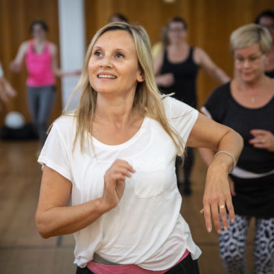 En medelsålders kvinna dansar i en grupp.