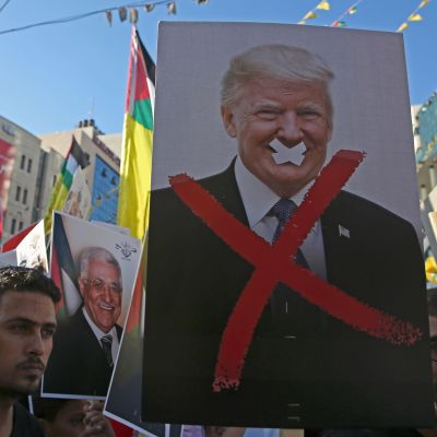 Palestinska demonstranter håller upp ett plakat med Donald Trump.