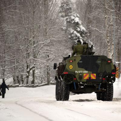 Suomen puolustusvoimien sotilaita sotilasajoneuvon kyydissä lumisessa kaupunkimaisemassa.