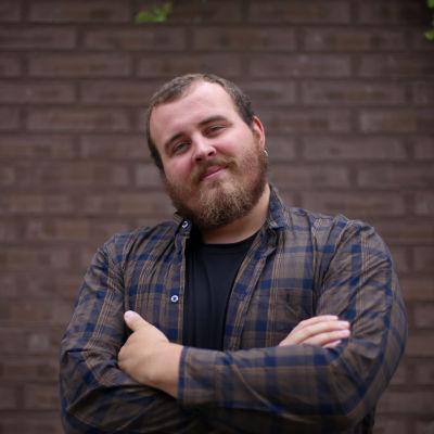 En man står framför en mur och ler