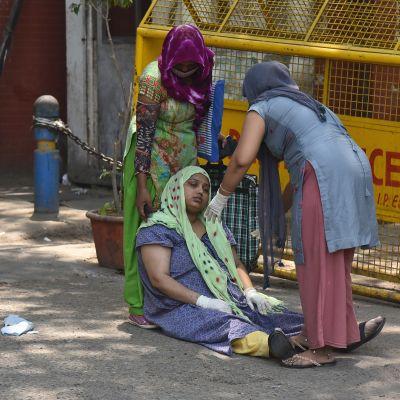 En covidsjuk kvinna sitter på marken utanför ett sjukhus. Två personer hjälper henne.