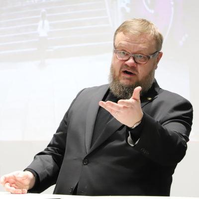 En skäggig medelålders man i mörk kostym och svart skjorta håller ena handen upplyft framför sig under ett tal från en scen.