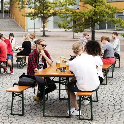 Människor sitter utomhus på en restaurangs uteservering.