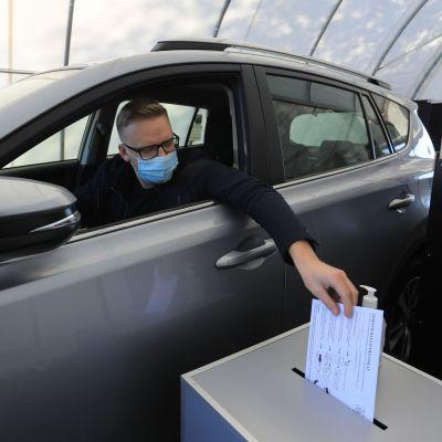 Mies jättää äänestyslipukkeen laatikkoon autokaistalla.