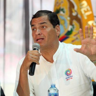 Bild på man i vit skjorta. Han talar i mikrofon.
