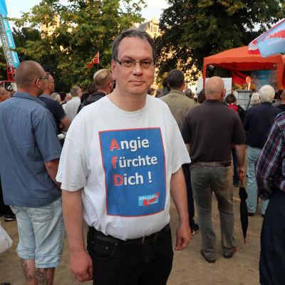 """En AfD-anhängare på ett valmöte i Schwerin i Mecklenburg-Vorpommern. """"Angie var rädd"""", står det på t-tröjan med hänvisning till Angela Merkel."""