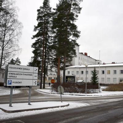 Norra Kymmenedalens sjukhus i Kouvola, en vit byggnad med träd i förgrunden. En ambulans kör förbi.