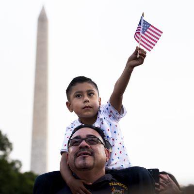 En pojke sitter på en mans axlar och viftar med en flagga.