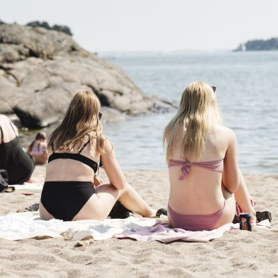 Kvinnor sitter på en solig strand i Solvik, Helsingfors, med ryggarna mot kameran.