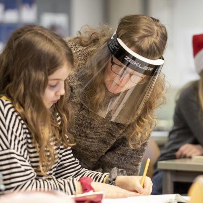 Opettaja Heidi Söderlund neuvomassa koululaista.