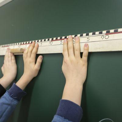 viivotin ja kädet ala-asteen oppilaat