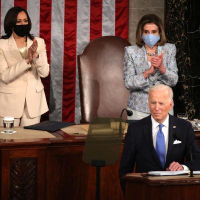 President Joe Bidens första tal till kongressen kretsade kring coronapandemin och ambitiösa sysselsättningsmål. Vicepresident Kamala Harris och talman Nancy Pelosi klappar i bakgrunden.