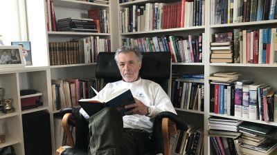 Jan-Erik Enestam sitter framför en bokhylla med en bok i handen.