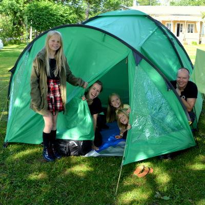 En kvinna, en man och tre barn som sitter inne och utanför ett grön tält.