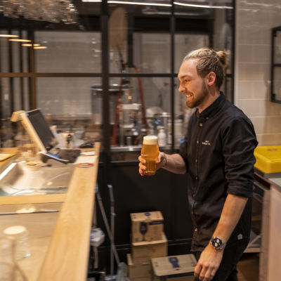 En man går med en öl i handen bakom en bardisk.