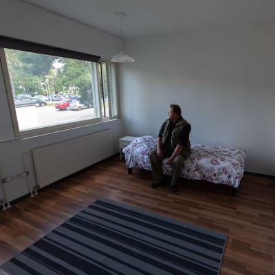 Kari Ahvenainen istuu sängyllään ja katsoo ikkunasta ulos.