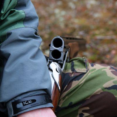 Maastopukuinen polvi, jonka päällä auki taitettu päällekkäispiippuinen metsästyshaulikko.